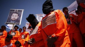 Former Guantanamo Bay detainees wear black hoods during a protest to demand the release of Yemeni detainees from Guantanamo Bay, outside the U.S. embassy in Sanaa April 16, 2013. (Reuters)